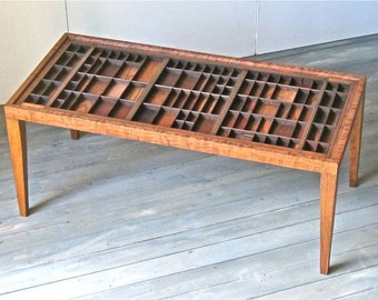 Custom made coffee table, cherry wood, in which you can display a collection under a lift out glass top made from printers type boxes.