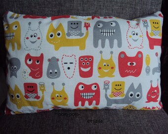 small rectangular cushion 33 x 22 theme monsters color red, mustard yellow, gray on white background