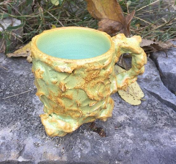 medium sized ceramic mug in golden orange and pale green