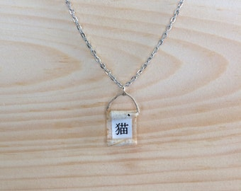 Cat in Japanese calligraphy on a white minimal necklace