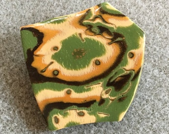 Dramatic polymer clay pin in an organic green, gold, brown, cream and copper design