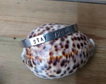 HANDMADE Smalle 0,7 cm. aluminium bangle armband met tekst ' stay true. ' polsmaat 15 - 17,5 cm. Geschuurd en gepolijst.
