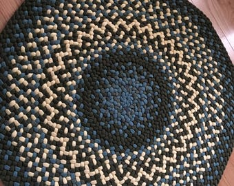 This is a round braided rug in light blue, yellow and army green.