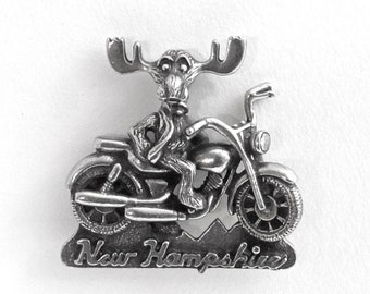 "Motorcycle riding Markie Moose tac pin ""New Hampshire"" - moose ridin' a big V twin machine through the hills of the Granite State"