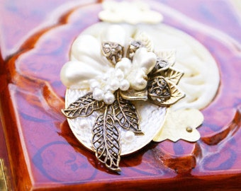 Beautiful antiqued filigree leaf detail with pearl floral bloom. Woven white background pin brooch.