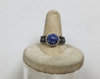 The ring has  10 mm Blue Sodalite in it. It is made of sterling silver size 9 1/2. this is the first ring with my new band.