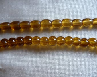 2 Strands of Glass Beads, Shades of Gold. Sold per 16 inch strands. The shapes are a 8x6 oval and 6mm round.