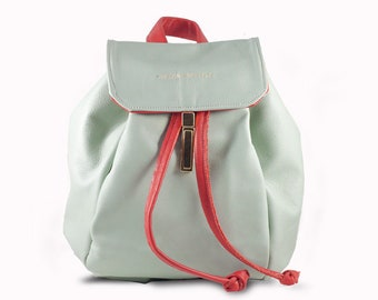 Handcrafted women's leather backpack with drawstrings and golden clasp closure.