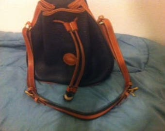 Dooney & Bourke drawstring bucket bag in navy all weather leather with British tan trim