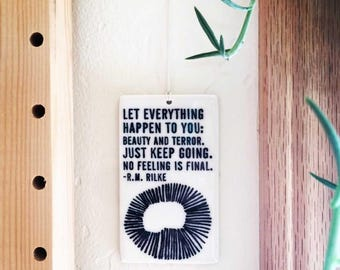 porcelain wall tag screenprinted text let everything happen to you: beauty and terror. just keep going. no feeling is final. -r.m. rilke