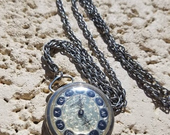 Vintage Nelson Swiss made pocket watch or pendant with Roman Numerals and ornate gold tone face, on chain
