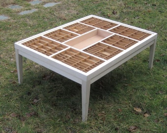 Large wood coffee table with a glass top that lifts out so you can display seashells, jewelry, stones and other collectibles.