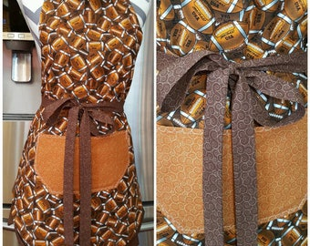 Adult Apron. Woman's Apron. Orange and brown footballs with orange and brown pocket, ties and frills.