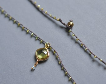 Gold and Peridot Green Dangle Charm with pale blue chalcedony drop on daintiest crocheted necklace in gold and brown
