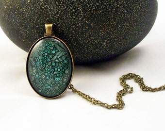 Teal Leaf and Circle Graphic Oval Glass Pendant Necklace