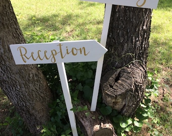 Two White Painted Rustic Wood Gold Wedding Reception Ceremony Sign on Stake Arrow Country Modern Cursive Script