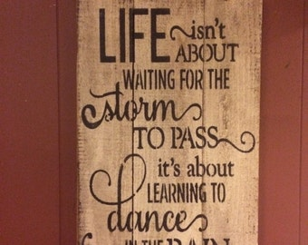primitive sign: LIFE isn't about waiting for the storm to pass its about learning to dance in the rain