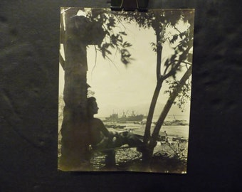 WWII Philippines Original Photo- Soldier Leaning against tree overlooking war ship in harbor