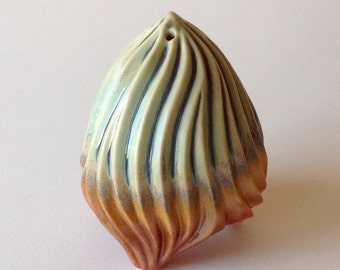 Carved porcelain salt shaker in green, tan & orange