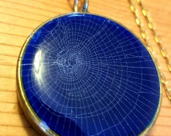 Real spiderweb on blue resin in brass necklace