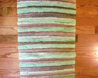 Rag rug with fringes.Woven greens and browns stripes pattern.Oblong