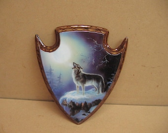 Wolf and the moon on a arrowhead plaque.