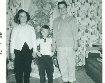1950s Christmas Brothers Sister Standing in Front of Tree Mid Century Holiday Vintage Black White Photo Photograph