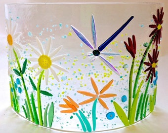 Glass arc with garden flowers and a dragonfly