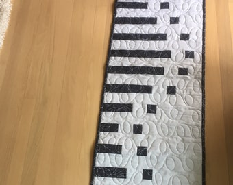 an awesome  wave table runner in light gray and charcoal .