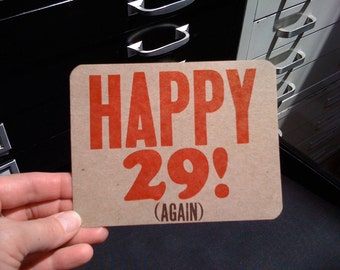 Happy 29 Again! Handmade Letterpress Printed Birthday Postcard in bright red and brown on light brown paper with cool rounded corners
