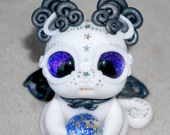 Glitter white and pearl black polymer clay wizard dragon sculpture with sparkly purple eyes, a starry cape and a crystal ball