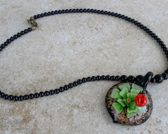 Ladybug necklace in black, green and red