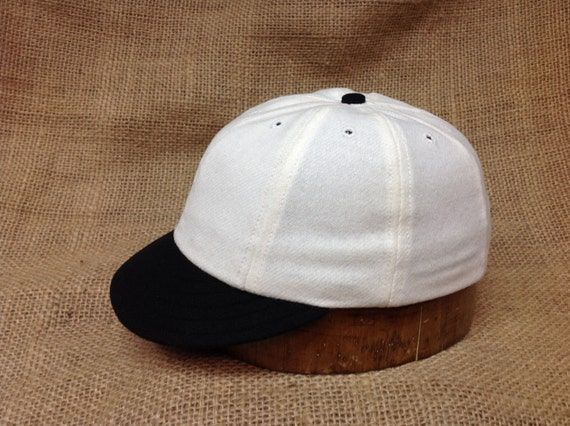 White wool flannel 8 panel cap with black 1910 visor. Fitted to any size.