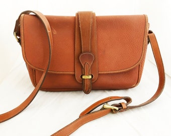 Dooney and Bourke - Leather Medium All weather leather British tan purse with adjustable shoulder strap