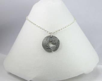 Brushed aluminum bird pendant.