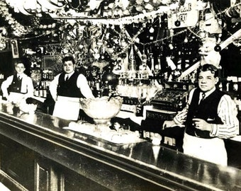 Babe Ruth (center) with his father, George Herman Ruth Sr, tend bar in Baltimore