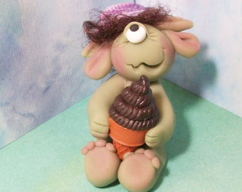 One eyed ice cream monster with brown hair and striped purple hat. polymer clay monster