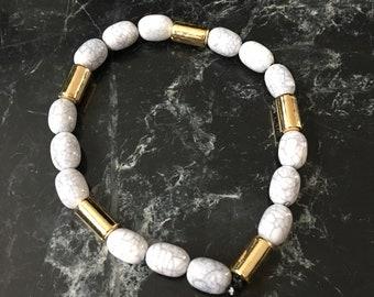 Handmade beaded bracelet in white/light gray beads with golden accent