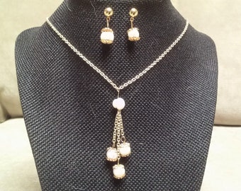 Set of necklace and earrings with three strands of Swarovski crystal pearls and single pearls for earrings.