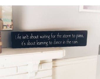 Life isn't about waiting for the storm to pass, its about learning to dance in the rain. 6x24 painted solid wood sign . Hung with 2 sawtooth