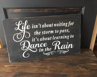 Life isn't about waiting for the storm to pass but learning to dance in the rain, wooden inspirational sign