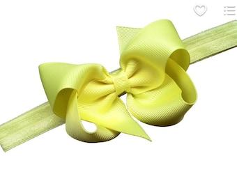 Yellow 3 inch pinwheel style bow on matching elastic headband