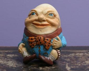 Humpty Dumpty jacket Plaid and purple bow figurine. Alice's Adventures in Wonderland. Lewis Carroll