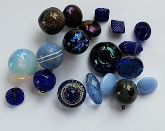 A mixture of different types of blue glass buttons. Ball buttons, opaline glass,iridescent glass, painted glass. From 1910 to 1950s.