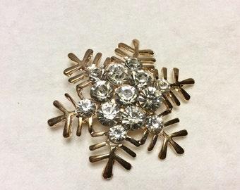 Vintage gold metal snowflake with clear rhinestones cluster brooch pin.