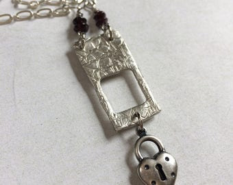 Garnet red and fine silver cut away pendant necklace.Heart lock charm, fine silver necklace.
