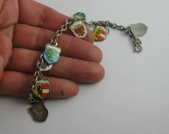 Charm bracelet: bracelet in silver (Ag 835) with 11 crest pendants made of silver and enamel. Length 17.7 cm. 70s souvenir bracelet. VINTAGE