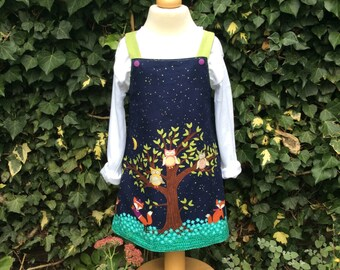 Reversible pinafore dress with white top.