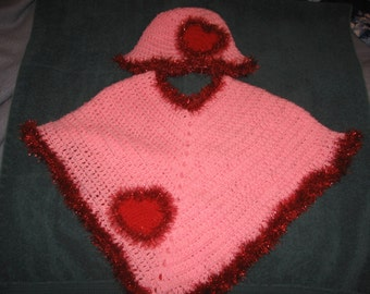 Rosa Poncho mit Hut und Fuzzy Herzen befestigt