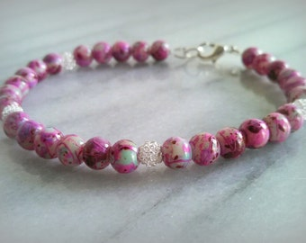 Multicolor splash beaded bracelet with silver coil wire bead accents.